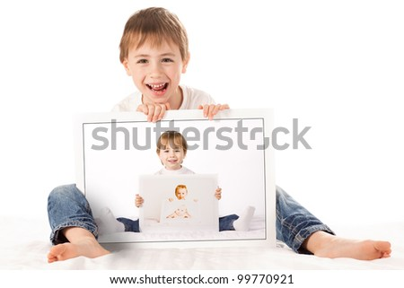 A cute  boy, sits on the floor, holding baby photographs of himself. The photographs are arranged such that the boy is holding a photo of his younger self, holding a photo of his baby self.