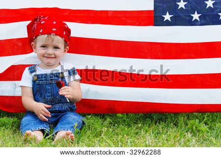 A cute boy sitting in front of an american flag