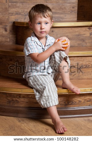 A cute boy with an orange in his hand sitting on the steps.