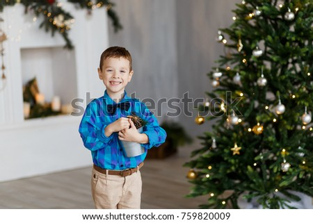 A cute boy with pinecones in front of the fur-tree with candles. New year's eve. Christmas eve. Cozy holiday at the fir-tree with lights and gold decor. #759820009