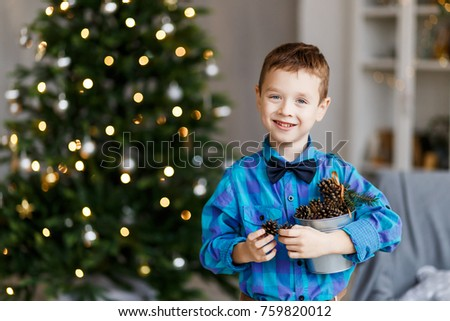 A cute boy with pinecones in front of the fur-tree with candles. New year's eve. Christmas eve. Cozy holiday at the fir-tree with lights and gold decor. #759820012