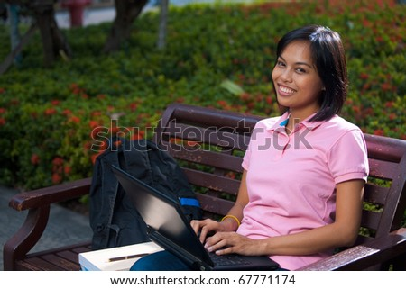 A cute college coed student sitting wearing pink shirt smiling and using her black laptop outside on a university campus bench. 20s female Asian Thai model of Chinese descent looking at camera
