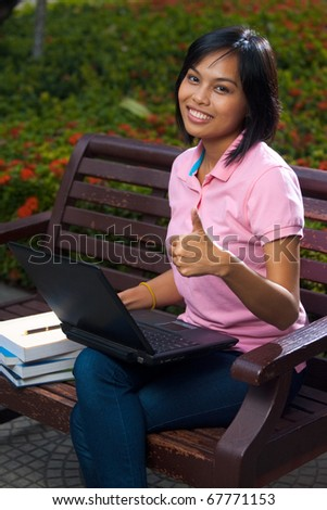 A cute college student using a laptop on a park bench gives a thumb up for success while beaming a radiant smile.  20s female Asian Thai model of Chinese descent.