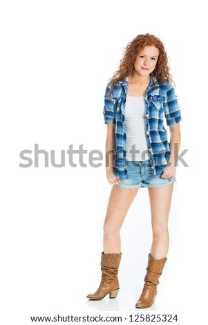 A cute country girl with natural red, curly hair wearing short denim shorts.
