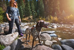 a cute dog and woman hiking next to a mountain stream in Colorado.
