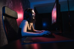 A cute female gamer girl sits in a cozy room behind a computer and plays games. Woman live streaming computer video games to her fans and wiggle hand to them. Streamer and gamer concept.