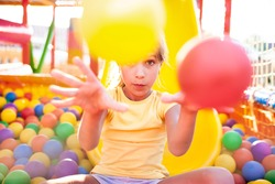 A cute funny girl sits in a playground with soft and bright equipment and throws colorful balls towards the camera