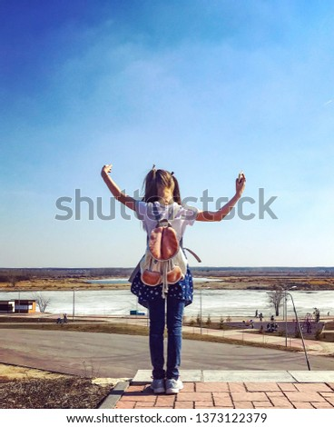 A cute girl admire a beautiful view of the frozen river and clear sky. Warm spring days
