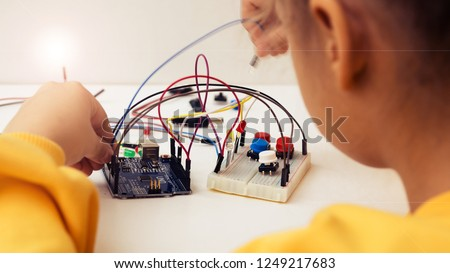 A cute girl constructs robot arduino and program it. The boards and microcontrollers are on the table. STEM education inscription. Programming. Mathematics. The science. Technologie. DIY.
