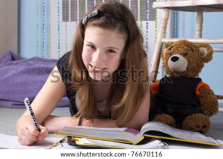 A cute girl does homework in her bedroom - stock photo