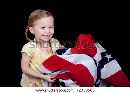A cute girl folding/holding the American Flag