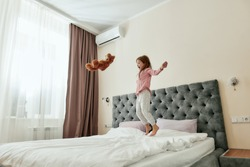 A cute girl having fun on a big bed throwing her teddybear up and jumping barefoot in a huge light room. Happy childhood concept