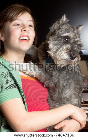 A cute girl holding a happy Miniature Schnauzer dog.