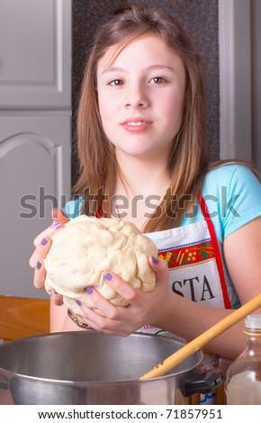 A cute girl holding dough preparing pizza - stock photo