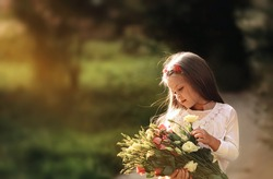 A cute girl is holding a large bouquet of plucked flowers. Portrait of a gentle angel in the summer sun.