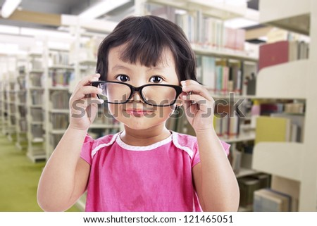 A cute girl is wearing glasses in school
