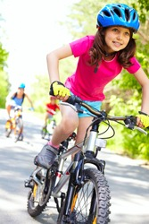 A cute girl riding her bicycle with competitors far behind