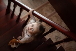 A cute girl with a toy dog in her hand stands on the steps of a wooden staircase in the interior of the house and looks up