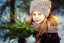 A cute girl with blond hair in a plaid coat and a cozy knitted hat and scarf in the forest in winter with a bouquet of fir branches, a magical fairytale atmosphere. Image with selective focus