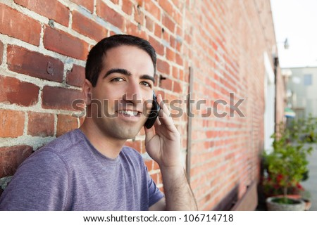 A cute guy on a mobile phone outdoors by a brick wall, looking at camera with a smile.