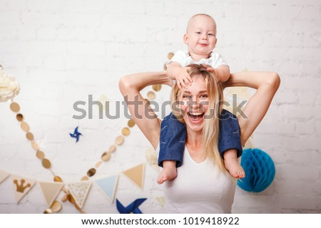 A cute handsome one-year-old baby sitting by her mother's neck grabs her by the hair and laughs. A beautiful young mother with her son play laughing and look at the camera. Mothers Day.