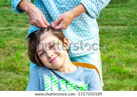 A cute happy boy is braided with long hair braids. Mom cares for her son's hair. Fashionable teenage youth hairstyles.