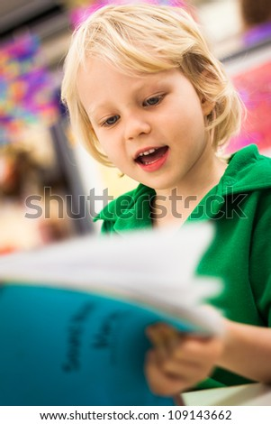 A cute happy young school boy reading a book in a class room.