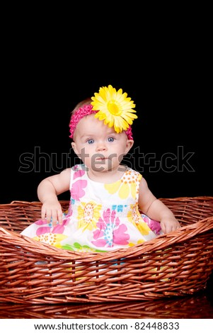 A cute image of an adorable baby with a yellow bow in her hair.  She is sitting in a basket.