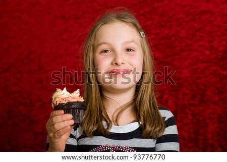 a cute kid eating a fresh baked cupcake with colorful frosting.