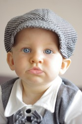 A cute little baby boy is looking at camera and is wearing a  chequered hat and suit. The baby has blue eyes. Use it for a parenting, love concept. Photo in vintage style.