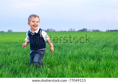 A cute little baby boy sit in the grass