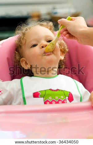 A cute little baby fed by her mother, eating spinach.
