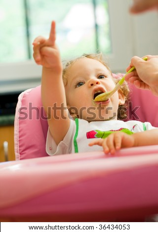 A cute little baby fed by her mother, eating spinach, pointing upward at somthing.