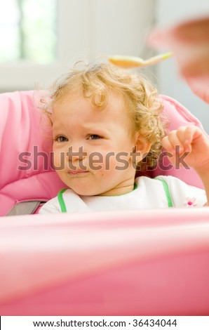 A cute little baby fed by her mother with a spoon, with a sad facial expression, she does not want to eat.