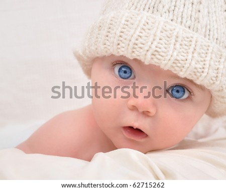 Stock Photo A cute little baby is looking into the camera and is wearing a white hat. The baby could be a boy or girl and has blue eyes. use it for a parenting or love concept.