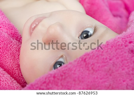 A cute little baby is looking into the camera in pink towel. The baby could be a boy or girl.