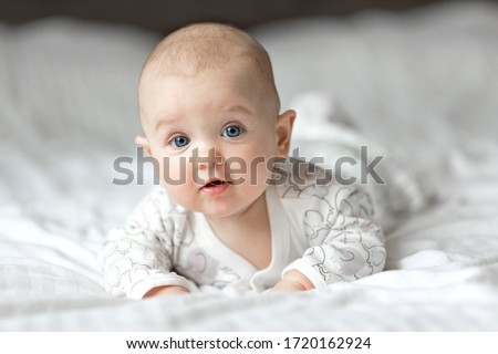 A cute little baby is smiling lying on the bed on a white sheet in the parents bedroom. Closeup portrait of newborn baby looking at camera