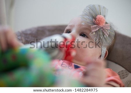 A cute little baby looking at the camera and playing and happy. The child looks around