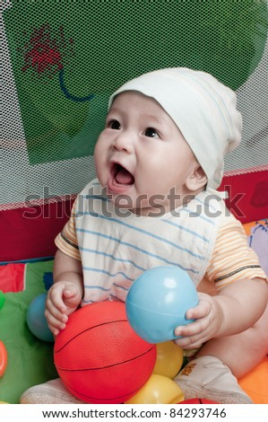 A cute little baby playing and smiling with a toy.