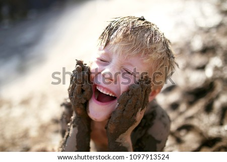 A cute little boy child is laughing as he plays outside in the mud and rubs dirt on his face with his hands. Stock photo ©