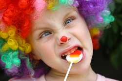 A cute little boy dressed up in a clown costume, making a silly face and eating a lollipop