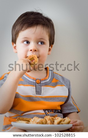 A cute little boy eats a homemade cookie indoors