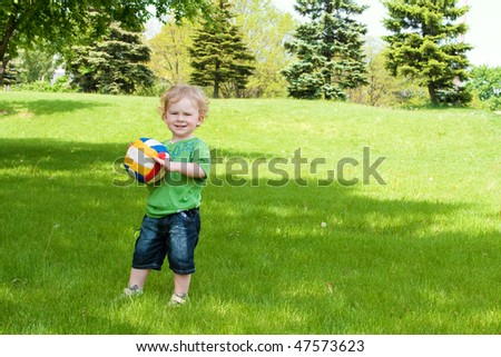 A cute little boy holding ball in a spring park