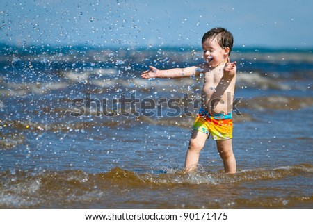 A cute little boy running through the water at the beach