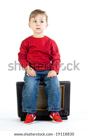 A cute little boy sitting on a vintage radio, isolated on a white background.