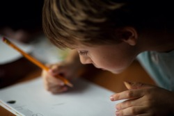 A cute little boy writing with a pencil close up