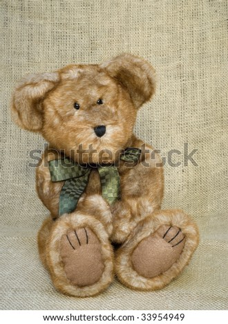A cute little brown toy stuffed bear with a green bow, vertical with copy space