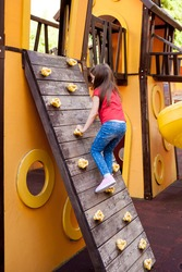 A cute little girl climbs an artificial wall in the playground on sunny summer day. rock climbing lessons for children. Kids having fun, playing outdoors and active lifestyle
