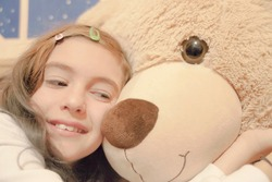 A cute little girl cuddling her big teddybear. Closeup shot.