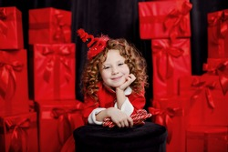 A cute little girl dressed like a little Santa holds lollipops in her hand and smiles. She has a red hat on her head. The girl on the background of a large number of red boxes in a gift box. Christmas